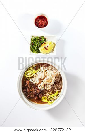 Traditional Vietnamese soup Pho Bo with beef meat, rice noodles, sturdy broth and a set of hot spices isolated on white background. Clear veal bouillon with noodle, meat and vegetables close up poster