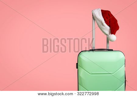 Plastic Suitcase And Santa Claus Hat On Red Background. Concept Of Travel To Visit Friends And Relat