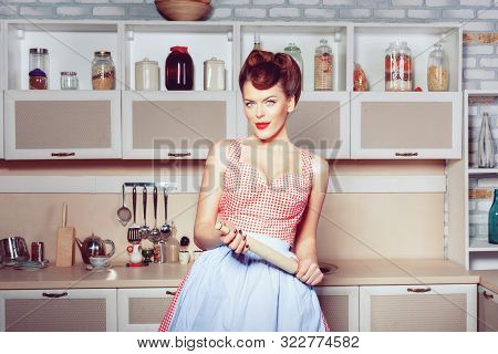 Woman Housewife In The Kitchen With A Rolling Pin. She Is A Retro Style Housewife.