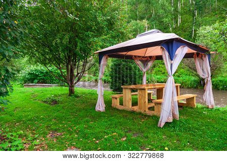Outdoor Tent With Furniture In The Forest With Trees And Green Grass During An Event, Wedding Or A C