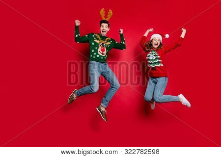 Full Length Photo Of Lady And Guy Jumping Excited By X-mas Discounts Wear Ugly Ornament Jumpers And