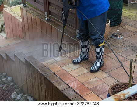 Woman Cleans Stone Slabs With A Pressure Washer
