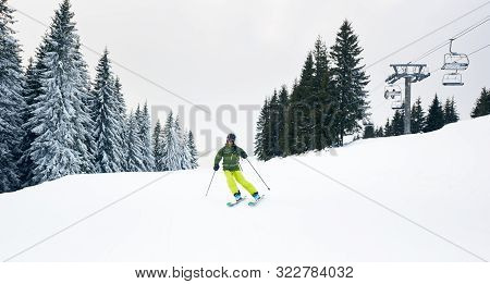 Male Skier Skiing On Ski Hillside At Resort After Taking Chairlift On Beautiful Snow-covered Mountai