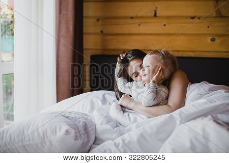 Happy Young Mother And Her Baby Playing In Bed With White Linens. Happy Family Concept.