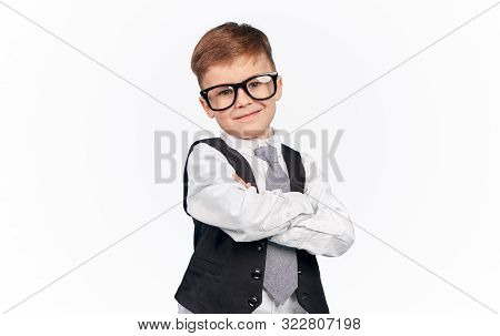 Smirking Kid In Glasses And Formal Outfit With Crossed Arms Standing Over White Background