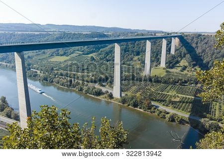 Panoramic View On High Freeway Viaduct Bridge Across Mosel River Valley And Terraced Vineyards, Road