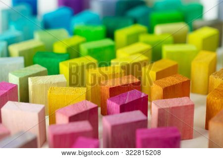 Spectrum of colorful wooden blocks standing, on white background.  Background image or cover for something creative or a diverse group.