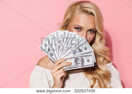 Image closeup of glamour seductive woman smiling while holding cash money at her face isolated over pink background