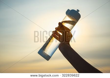 Human Hand Holds A Water Bottle Against The Setting Sun. Close Up Of A Reusable Water Bottle In A Hu