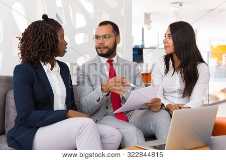 Legal Expert Explaining Contract Detail To Young Colleagues. Business Man And Woman Sitting On Offic