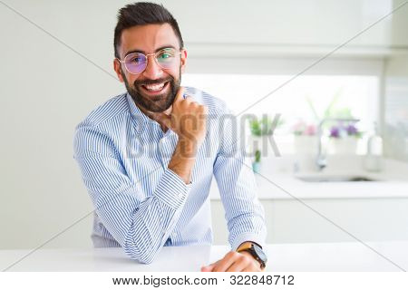 Handsome business man wearing glasses and smiling cheerful with confident smile on face