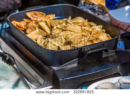 Chinese Potstickers Cooking In A Pan At A Food Market