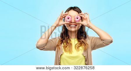people, fast food and fun concept - happy asian young woman with donuts instead of eyes over blue background