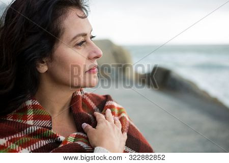 Thoughtful woman wrapped in shawl on beach during winter