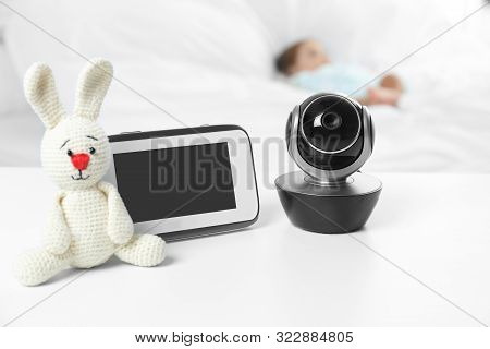 Baby Monitor, Camera And Toy On Table Near Bed With Child In Room. Video Nanny