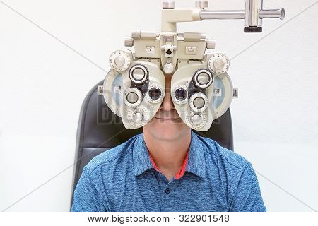 Caucasian Man  Checks Eyesight In A Clinician Oculist. Man Checks His Vision On The Machine Checking
