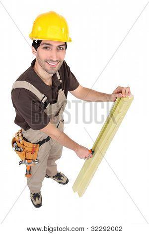 Carpenter measuring plank of wood