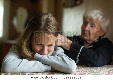 A crying little girl is comforted by her grandmother.