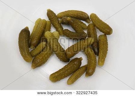 Mini Pickled Cucumbers Preserved In Brine On A White Plate