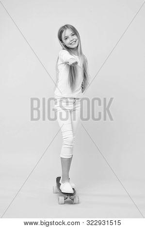 Kid Adorable Child Long Hair Adore Ride Penny Board. Girl Likes To Ride Skateboard. Active Leisure O