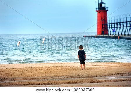 Little Boy Stands, On The Shores Of Lake Michigan, Staring At The South Haven Lighthouse.  His Feet