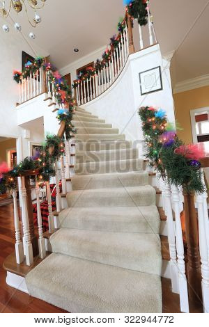 The stairway is the focal point of this beautifully decorated interior of a residential home.  Bright lights and colorful bows are festive for the Christmas holiday.