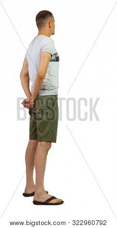 Back view of young manin shorts looking. Rear view people collection. backside view of person. Isolated over white background. A guy in shorts is clasped hands behind his back.