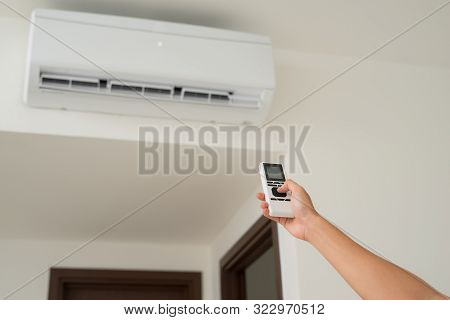 Air Conditioner Inside Unit With Man Operating Remote Controller. / Air Conditioner With Remote Cont