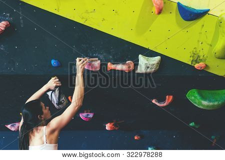Young Athletic Woman Cleans Boulder Holds By Brush In Boulder Gym.