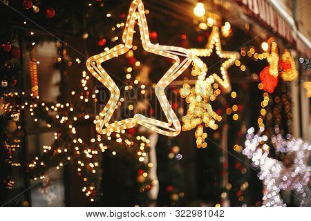 Stylish Christmas Golden Star Illumination And Fir Branches With Red And Gold Baubles, Golden Lights