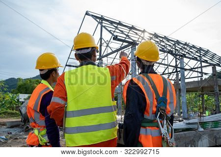 Construction Workers Wearing Safety Clothing And Discussing On Construction Site Checking Office Lap