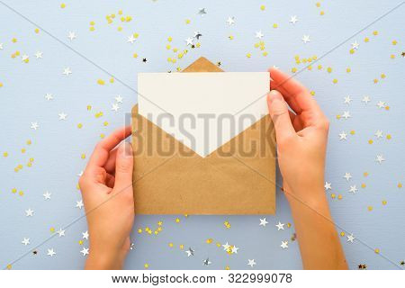 Female's Hands Holding Kraft Paper Envelope Letter With Blank White Card Mockup Over Pastel Blue Bac