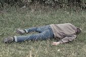 The corpse of a tramp in the grass. Criminal. Alcoholic intoxication. Killing a homeless man. dead body after lightning strike poster