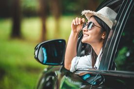 Happy Woman Hand Holding Hat Outside Open Window Car With Green Forest Woods Mountain Background. Pe