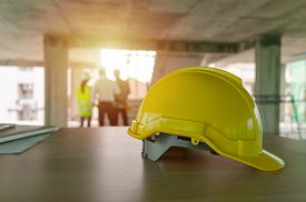 Yellow Safety Helmet On Workplace Desk With Construction Worker Team Engineer Or Inspector Checking