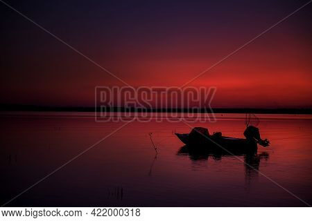 The Motorboat Was Moored To The Shore. Bright Red Sunset On The Lake. Calm And Peaceful. Sport Fishi