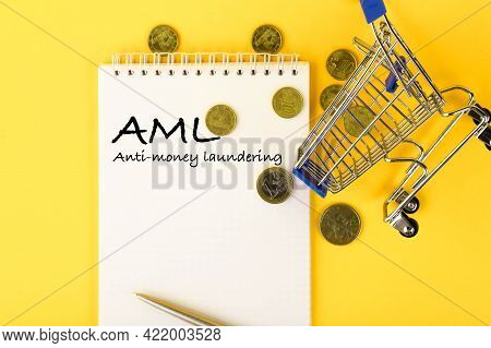 Abbreviation Aml Anti Money Laundering, Written On A Notepad With Coins And A Shopping Cart.