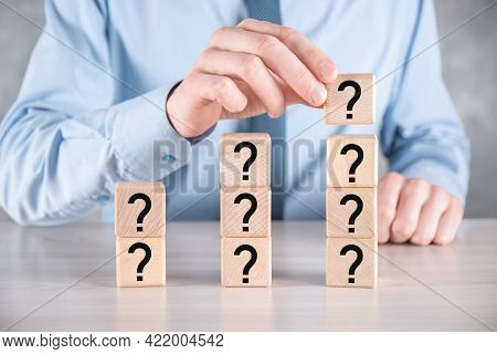 Businessman Hold And Put Wooden Cube Block Shape With Question Marks On Grey Table. Space For Text.c