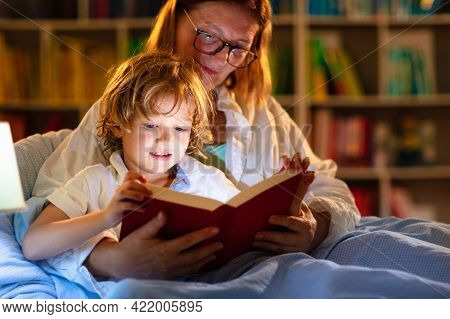 Mom And Child Reading Book In Bed. Kids Read.