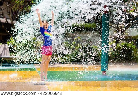 Child Playing Under Tip Bucket In Water Park.