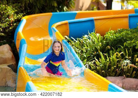 Kids On Water Slide In Aqua Park. Children Having Fun On Water Slides On Family Summer Vacation In T
