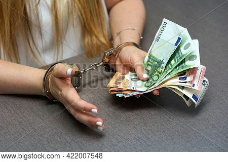Woman Office Worker In Handcuffs Holding A Bribe Of Euro Banknote. Close-up Woman Hands In Handcuffs