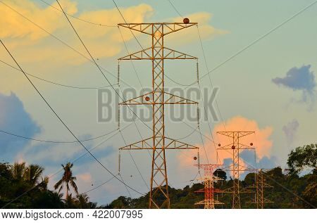 Silhouette Of Electricity Pylon With Morning Sunrise. Distribution Electric Substation With Power Li