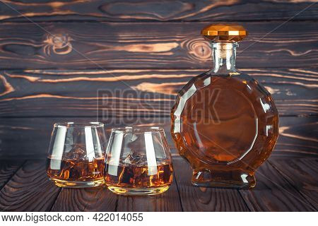 A Bottle Of Whiskey And Two Glasses On A Dark Brown Wooden Table. Transparent Yellow Alcoholic Bever