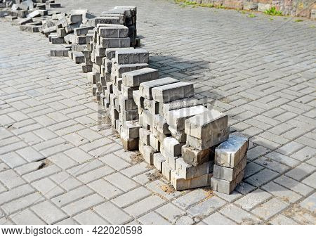 Repair Pavement On Street Or Square. Long Stack Of Disassembled Paving Tiles Crosses Image Diagonall