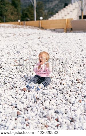 Funny Kid In A Pink Blouse And Blue Pants Sits On A Pebble Beach And Holds A Pebble In His Hand Agai
