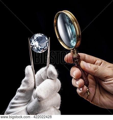 Large gemstone and loupe in jeweler's hands close up. Gem identifying and evaluating process.