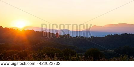 Beautiful Panoramic Mountain Landscape With Hazy Peaks And Foggy Valley At Sunset.