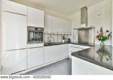 Well Organized Small Home Kitchen Interior With Sink And Light Furniture With Stove In Urban Apartme