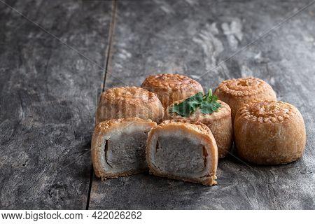 Mini  Melton Mowbray Pork Pies On Rustic Wooden Table